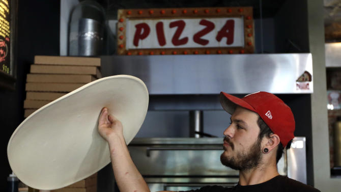 In this Wednesday, Sept. 12, 2012 photo, Joseph Hunter tosses a pizza in the air at Pizza Brain in Philadelphia.  Hundreds of people turned out for the grand opening of Pizza Brain this month in Philadelphia's Fishtown neighborhood. It's a restaurant where visitors can eat a slice or two of artisan pie while gawking at a pizza-related photos, records, knickknacks and videos.  (AP Photo/Matt Rourke)