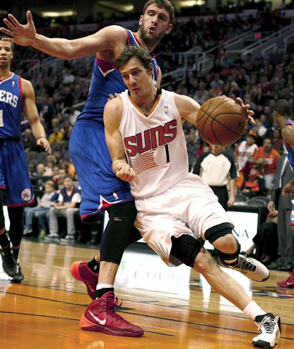 Phoenix Suns guard Goran Dragic (1) drives past Philadelphia 76ers center Spencer Hawes (00) during the third quarter of an NBA basketball game Saturday, Dec. 28, 2013, in Phoenix