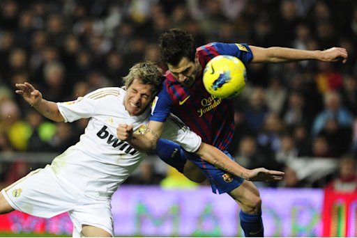 Barcelona's Cesc Fabregas (R) heads the ball and scores against Real Madrid