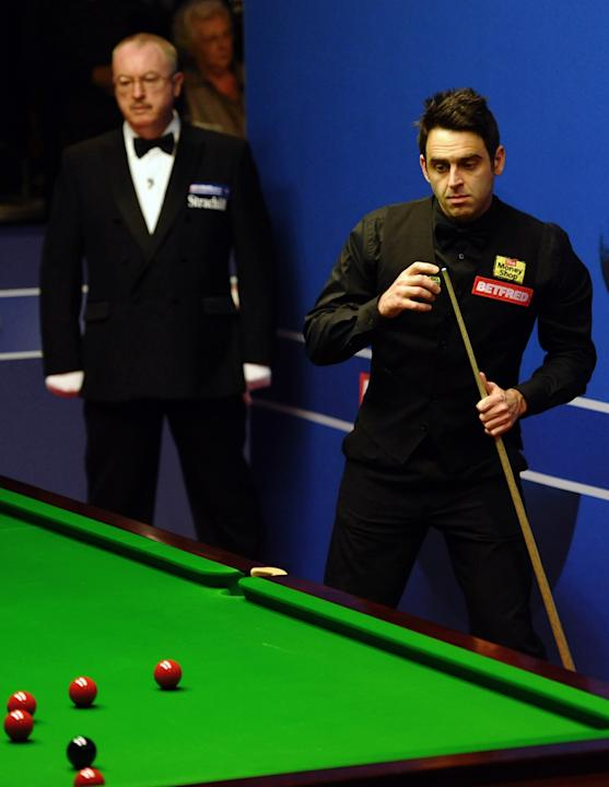 Ronnie O'Sullivan of England (R) prepares to play a shot during a first round match of the World Championship Snooker tournament against Peter Ebdon of England at the Crucible Theatre in Sheffield, no