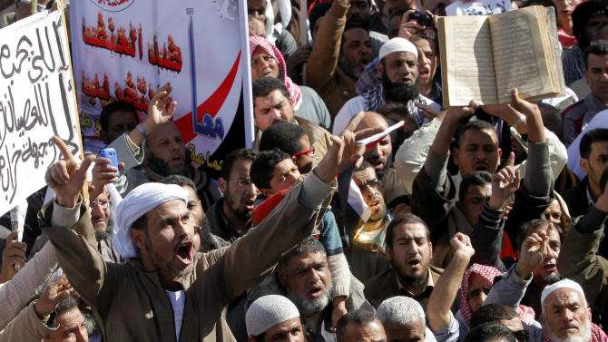 An Egyptian Islamist protester shouts slogans supporting President Mohammed Morsi during a rally outside Cairo University in Cairo, Egypt, Friday, Feb. 15, 2013. Around 5,000 mostly hardline Islamists are rallying in Egypt against a recent wave of protests that has killed around 70 people. Arabic at background reads 'together against violence.' (AP Photo/Amr Nabil)