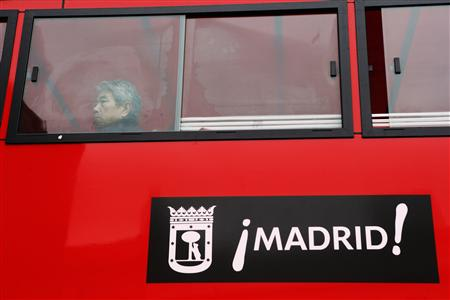 A tourist looks at sights as he rides a Madrid sightseeing bus in central Madrid January 8, 2013. REUTERS/Susana Vera