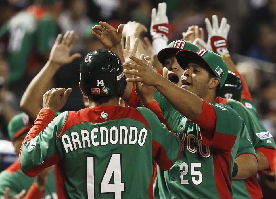 Mexico's Eduardo Arredondo (14) celebrates scoring a run against the United States with teammates, including Walter Ibarra (25) in the first inning during a World Baseball Classic baseball game on Friday, March 8, 2013, in Phoenix. (AP Photo/Ross D. Franklin)