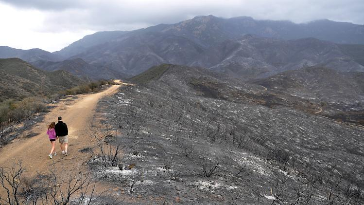 Hikers walk along a fire road in the burned area of the Santa Monica Mountains National Recreation Area in Newbury Park, Calif., on May 6,2013. Investigators ruled out arson as the cause of the fire that charred 44 square miles at the western end of the Santa Monica Mountains. (AP Photo/Tina Burch)