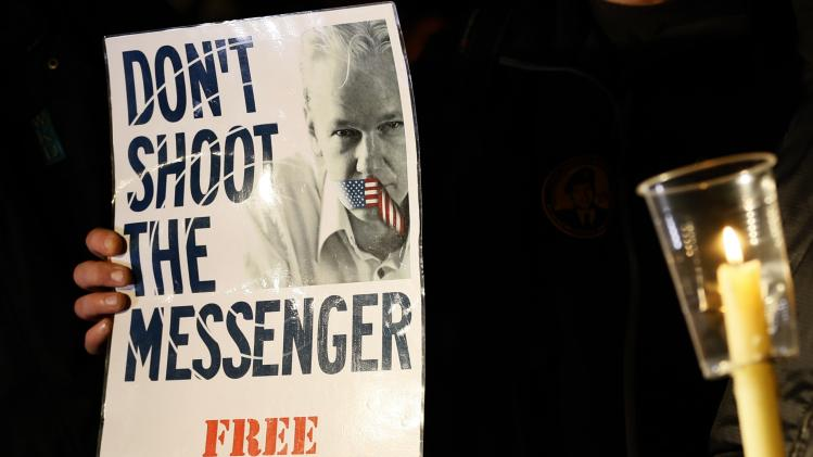 A supporter holds a banner as he waits for Julian Assange, founder of WikiLeaks to speak to the media and members of the public from a balcony at the Ecuadorian Embassy in London, Thursday, Dec. 20, 2012. Assange who faces extradition to Sweden over sexual assault, claims which he denies, took refuge in the embassy in June. (AP Photo/Kirsty Wigglesworth)