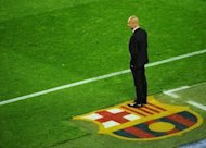 Barcelona&#39;s coach Josep Guardiola watches his team play Chelsea during the UEFA Champions League second leg semi-final football match Barcelona against Chelsea at the Cam Nou stadium in Barcelona on April 24. Guardiola is likely to announce on Friday whether he is staying or leaving the club, a source close to the team said Thursday