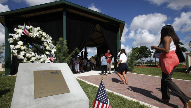 People gather to mark the 10th anniversary of the Sept. 11 terror attacks and to unveil a 9-11 memorial, Sunday, Sept. 11, 2011 in Pembroke Pines, Fla. Hundreds of little memorials to Sept. 11 have bloomed across the country in the intervening years since the terror attacks. But in some towns like this one, what began as a simple tribute to the dead turned into an expensive headache as the cost of building the memorial kept rising and the economy deteriorated. (AP Photo/Wilfredo Lee)