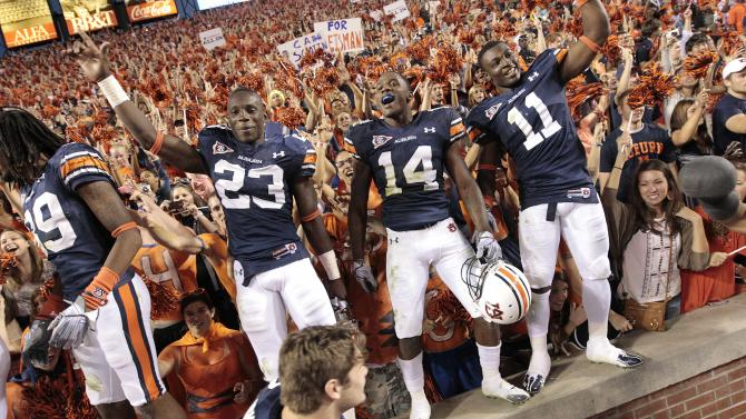 ** CAPTION CORRECTION, CORRECTS AMOUNT SPENT ON PROGRAM TO $28 MILLION, NOT $18 MILLION AND REMOVES RANKING ** FILE - In this Saturday, Oct. 16, 2010 file photo, Auburn players Onterio McCalebb (23) Demond Washington (14) and Chris Davis (11) react after their 65-43 win over Arkansas in an NCAA college football game in Auburn, Ala. According to statistics from the Department of Education, Auburn spends $28 million on their football program. (AP Photo/Dave Martin)