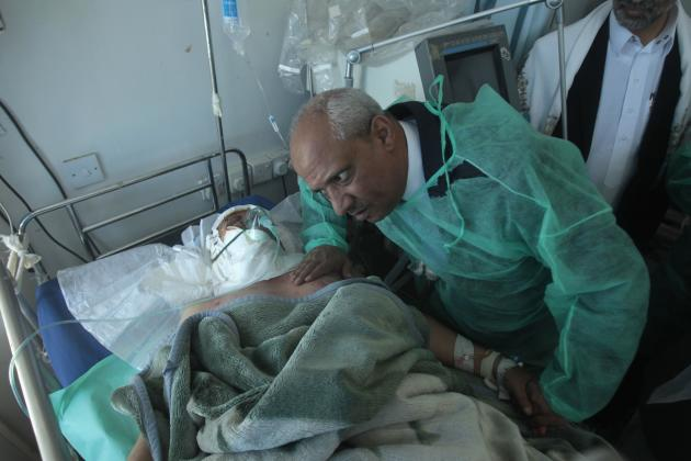 Yemen's Health Minister al-Ansi listens to army officer, injured in attack on Defence Ministry's compound, at a hospital in Sanaa