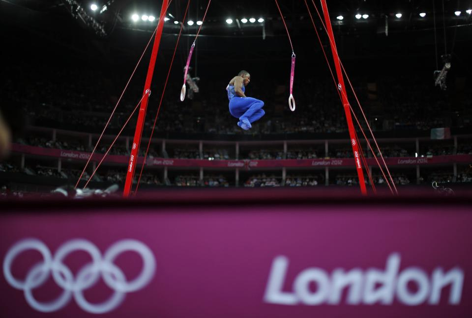 U.S. gymnast John Orozco jumps off after performing on the rings during the Artistic Gymnastics men's qualification at the 2012 Summer Olympics, Saturday, July 28, 2012, in London. (AP Photo/Matt Dunham)