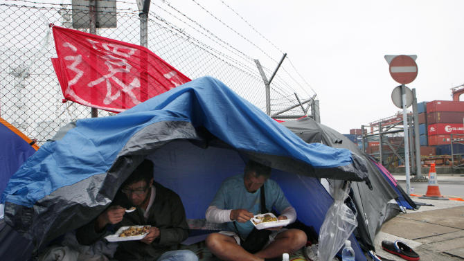Several hundred dockworkers and supporters camp out on a road in front of a container terminal on the seventh day of their strike in Hong Kong Wednesday, April 3, 2013. The strike by Hong Kong dockworkers that is slowing cargo shipments at the world's third busiest port looks set to drag into a second week. (AP Photo/Kin Cheung)