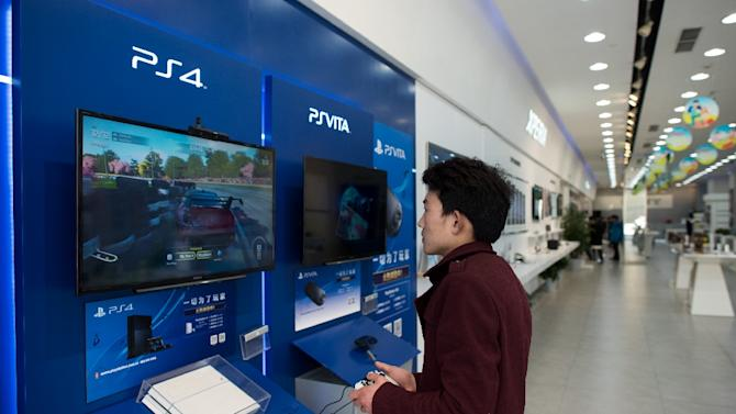 A man plays with a Sony PlayStation 4 in a shop in downtown Shanghai on March 19, 2015