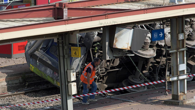 A railway worker walks next to a train which derailed at a station in Bretigny-sur-Orge, south of Paris, Saturday, July 13, 2013. An official on Saturday said a faulty rail joint may have caused a train derailment outside Paris that left six people dead and injured dozens. (AP Photo/Thibault Camus)