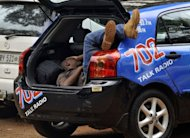 A man working for a local radio rests in the trunk of a car while members of the media wait to see South African Olympic sprinter Oscar Pistorius outside a Pretoria Police Station from about 5am on February 25, 2013. Pistorius met South African probation officers on Monday and discussed conditions to restart training as he awaits trial for the murder of his girlfriend, a prisons spokesman said