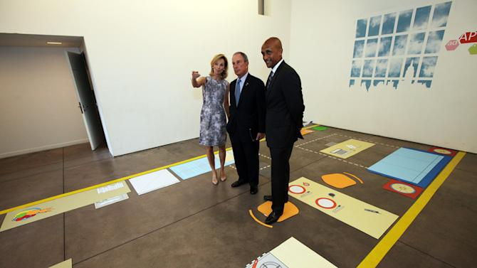 In this photo provided by the New York Mayor's office, Mayor Michael Bloomberg, center, stands with Amanda Burden, left, Department of City Planning Director, and Commissioner Mathew Wambua, Department of Housing Preservation and Development, in the kitchenette area of a full-scale mockup of a 300 square foot apartment on Monday, July 9,  2012 in New York.  The city is asking developers to propose ways to build such tiny units in the hopes of changing city code to accommodate cash-strapped singles and couples. (AP Photo/New York Mayor's Office, Edward Reed, Handout)