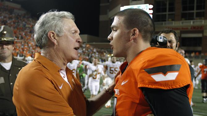 Texas coach Mack Brown, left, talks with Oklahoma State quarterback J.W. Walsh following an NCAA college football game in Stillwater, Okla., Saturday, Sept. 29, 2012. Texas won 41-36. (AP Photo/Sue Ogrocki)