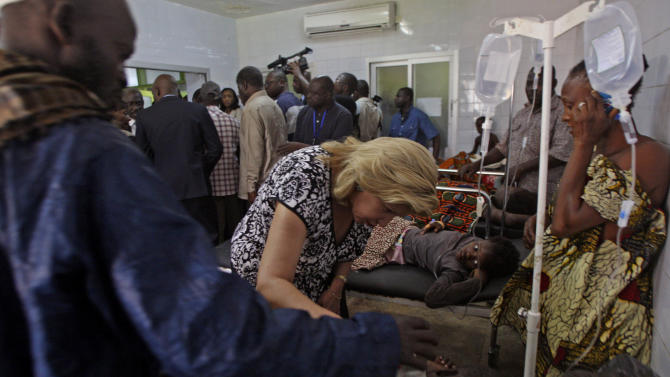 Ivory Coast First Lady Dominique Ouattara, center left, speaks with a person injured in a stampede as they are treated at a hospital in Abidjan, Ivory Coast, Tuesday, Jan. 1 2013. At least 61 people were killed early Tuesday in a stampede following a New Year's fireworks display in Abidjan, Ivory Coast's commercial center, said officials. The death toll is expected to rise, according to rescue workers. (AP Photo/Emanuel Ekra)