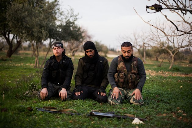 FSA fighters pray after an attack on a Military Academy in Tal Sheer village, north of Aleppo province, Syria, Thursday, Dec 13, 2012. (AP Photo / Manu Brabo)