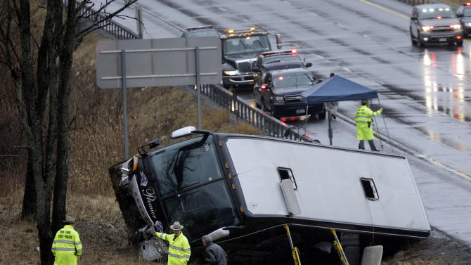 Law enforcement personnel work at the scene of a bus crash on the Adirondack Northway on Tuesday, March 12, 2013, in Clifton Park, N.Y.  State transportation officials say the accident happened just before noon Tuesday. Police had no other information about the accident or any injuries. (AP Photo/Mike Groll)