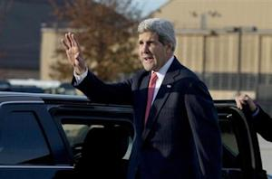 U.S. Secretary of State John Kerry waves before getting into his motorcade vehicle as he arrives at Andrews Air Force Base