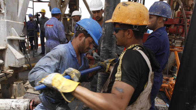 Oil workers work at Zubair oil field near Basra, 550 kilometers (340 miles) southeast of Baghdad, Iraq, Sunday, May 15, 2011. State-run Iraqi Drilling Company started Sunday drilling new wells in Iraq's 4.1 billion barrels Zubair oil field near Basra.IDC was awarded a nearly $250,000-deal last year to drill 23 new wells and to workover 63 other wells due to be completed in the coming two years.It has deployed four drilling rigs and four workover rigs. The field was among nearly a dozen oil fields Iraq awarded in 2009 during two International energy bidding rounds. It is being developed by Italy's Eni and partners Los Angeles-based Occidental Petroleum Corp. and South Korea's KOGAS. (AP Photo/Nabil al-Jourani)