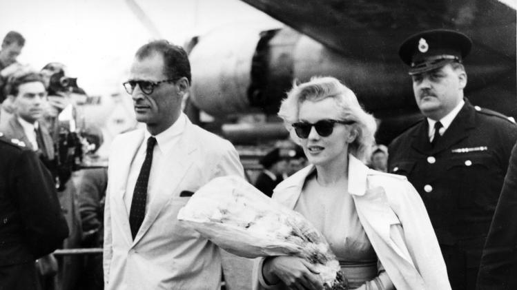 FILE - In this July 14, 1956 file photo, Hollywood actress Marilyn Monroe and her husband, playwright Arthur Miller, arrive from New York at London airport, England.  Monroe is in Britain to work on a movie.  In late 2012, the FBI has released a new version of files it kept on Monroe that reveal the names of some of her acquaintances who had drawn concern from government officials and members of her entourage over their suspected ties to communism. (AP Photo, File)