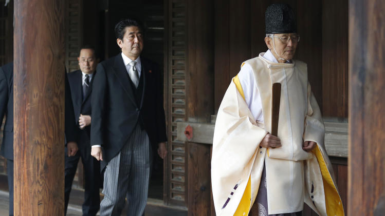 "FILE - In this Dec. 26, 2013, file photo, Japanese Prime Minister Shinzo Abe, second from right, follows a Shinto priest to pay respect for the war dead at Yasukuni Shrine in Tokyo. Abe visited Yasukuni war shrine in a move sure to infuriate China and South Korea. The visit to the shrine, which honors 2.5 million war dead including convicted class A war criminals, appears  to be a departure from Abe's ""pragmatic"" approach to foreign policy, in which he tried to avoid alienating neighboring countries. China and Japan are engaged in a war of words on editorial pages around the world. Beijing has taken aim at a recent visit by Japan's leader to a divisive war shrine, and Tokyo has answered back. (AP Photo/Shizuo Kambayashi, File)"