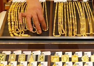 A sales girl arranges gold necklaces in a shop in Huaibei, …