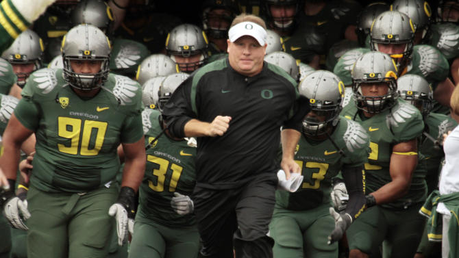 FILE - In this Sept. 17, 2011 file photo, Oregon head football coach Chip Kelly leads the team onto the field for an NCAA college football game against Missouri State in Eugene, Ore. The NCAA has taken away a scholarship and placed Oregon's football program on probation for three years for recruiting violations under previous coach Chip Kelly. The NCAA's Division I Infractions Committee released a report on Wednesday, June 26, 2013, that found Kelly and the university failed to monitor the program. (AP Photo/Don Ryan, File)