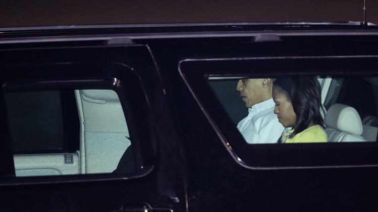 President Barack Obama and first lady Michelle Obama leave Honolulu Joint Base Pearl Harbor-Hickam in Honolulu, after arriving for the start of their holiday vacation, Saturday, Dec. 22, 2012. (AP Photo/Gerald Herbert)