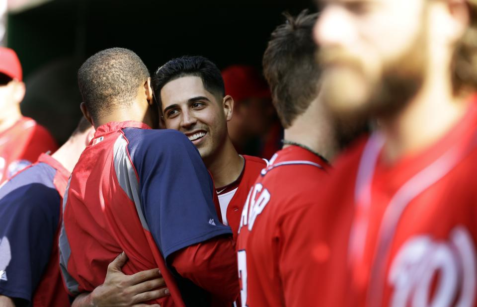Washington Nationals starting pitcher Gio Gonzalez, hugs fellow pitcher Edwin Jackson during the seventh inning of a baseball game against the Milwaukee Brewers at Nationals Park Saturday, Sept. 22, 2012, in Washington. It was Gonzalez's 20th win of the season, and the Nationals won 10-4. (AP Photo/Alex Brandon)