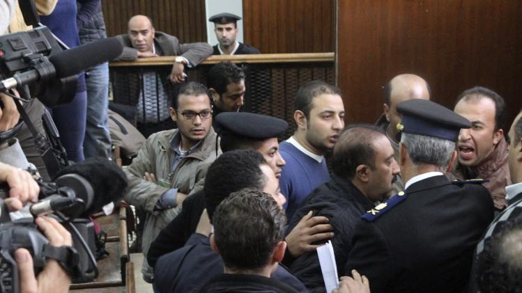 Members of the Muslim Brotherhood argue with policemen during the trial of the Brotherhood leaders in Cairo
