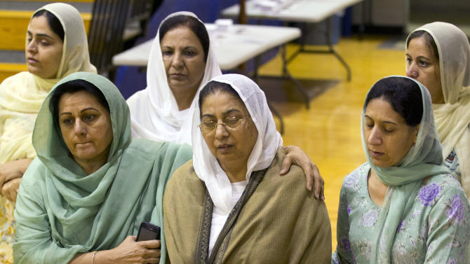 Mourners grieve at the funeral and memorial service for the six victims of the Sikh Temple of Wisconsin mass shooting in Oak Creek, Wis., Friday, Aug 10, 2012. The public service was held in the Oak Creek High School. Three other people were wounded in the shooting last Sunday at the temple. (AP Photo/Jeffrey Phelps)