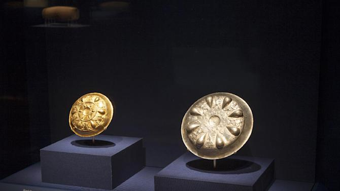 In this image provided by The Smithsonian Institution, a gold bowl from the Oxus Treasure, left, and a silver bowl with winged lions and heads of the Egyptian deity Bes are seen on display at the Smithsonian's Freer Sackler Gallery in Washington. The items go with a exhibit along with the Cyrus Cylinder, a 2,500-year-old Babylonian artifact sometimes described as the world's first human rights charter will be shown for the first time in the United States, beginning with the Smithsonian's Freer Sackler Gallery, followed by stops in New York, Houston and Los Angeles. The British Museum is loaning the Cyrus Cylinder, which carries an account of how Persian king Cyrus conquered Babylon in 539 B.C. and restored people held captive to their homelands. (AP Photo/The Smithsonian Institution, John Tsantes)