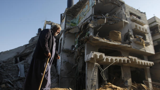 An elderly Palestinian walks next to a destroyed building after an Israeli strike in Gaza City, Tuesday, Nov. 20, 2012. Efforts to end a week-old convulsion of Israeli-Palestinian violence drew in the world's top diplomats on Tuesday, with President Barack Obama dispatching his secretary of state to the region on an emergency mission and the U.N. chief appealing from Cairo for an immediate cease-fire. (AP Photo/Hatem Moussa)