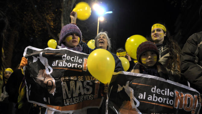 """People demonstrate against abortion legalization in downtown Montevideo, Uruguay, Monday, Sept. 24, 2012. Demonstrators protested the day before a congressional bill legalizing abortion is voted on. The signs read in Spanish """"not to abortion."""" (AP Photo/Matilde Campodonico)"""