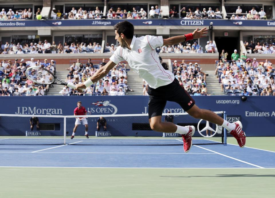 Novak Djokovic, of Serbia, goes airborne to return a shot to Stanislas Wawrinka, of Switzerland, during the semifinals of the 2013 U.S. Open tennis tournament, Saturday, Sept. 7, 2013, in New York. (AP Photo/Charles Krupa)