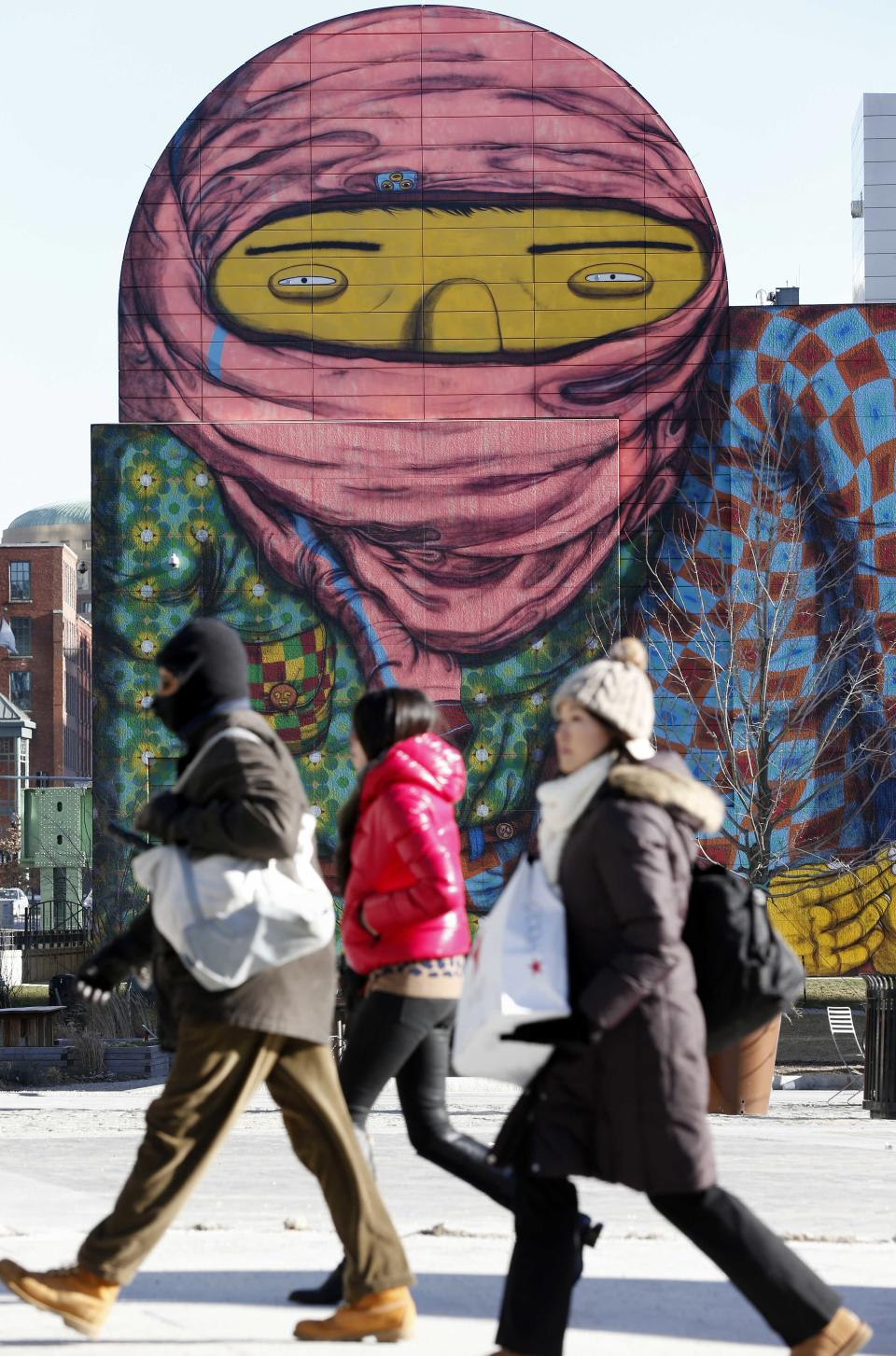 People walk past a mural painted on the side of a building in Boston, Wednesday, Jan. 23, 2013.  The National Weather Service says it's not expected to get above 17 degrees in Boston, with the wind chill making it feel five below.  (AP Photo/Michael Dwyer)