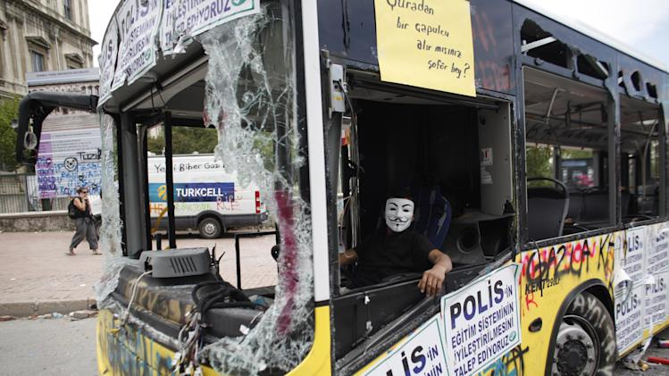 "A protester sits in a damaged bus at  Taksim square of Istanbul, Thursday, June 6, 2013.  The placards read ""We demand the improvement of the education system in the police"" . The Turkish officials, scrambling to contain tensions, have delivered more conciliatory messages to thousands of protesters denouncing what they say is the government's increasingly authoritarian rule and its meddling in lifestyles. (AP Photo/Kostas Tsironis)"