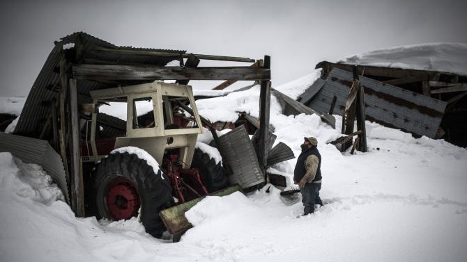 Jim Lippert looks at a collapsed structure on his farm following a massive snowstorm in Cowlesville