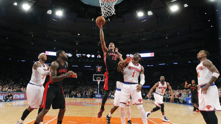 Toronto Raptors' DeRozan drives past New York Knicks' Stoudemire for a layup during their NBA basketball game in New York