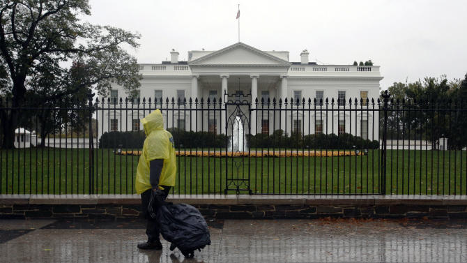 In this Monday, Oct. 29, 2012, photo, a lone man wearing a rain pouch walks past the White House in Washington, Monday, Oct. 29,2012, during the approach of Hurricane Sandy. Whoever wins the U.S. presidential election will likely struggle to manage the biggest economic threats he'll face. That's the cautionary message that emerges from the latest Associated Press Economy Survey. (AP Photo/Jacquelyn Martin)