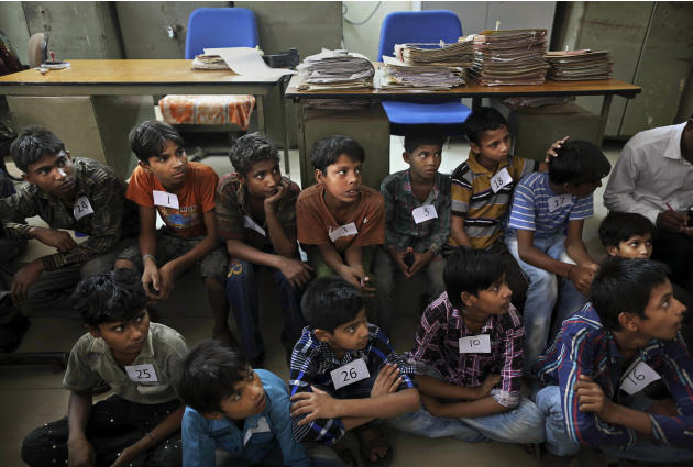 Young Indian bonded child laborers sit on the floor of the district magistrates office as they wait to be processed after being rescued during a raid by workers from Bachpan Bachao Andolan or Save the