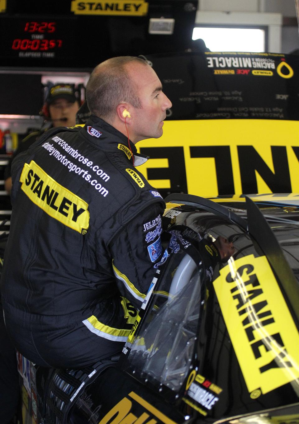 NASCAR driver Marcos Ambrose emerges from his car after practicing for Sunday's NASCAR Toyota Save Mart 350 auto race, Friday, June 24, 2011, at Infineon Raceway in Sonoma, Calif. (AP Photo/Ben Margot)