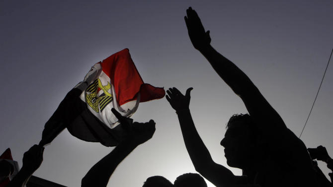 Egyptian protesters shout anti-Muslim brotherhood slogans and wave a national flag during a protest against the new judiciary law at the high court in Cairo, Egypt, Monday, June 3, 2013.(AP Photo/Amr Nabil)