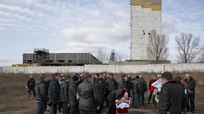 Relatives of a miner killed in an explosion on Wednesday at more than 1,000 meters (3,200 feet) underground at the Zasyadko mine, background, cry next to his coffin during a funeral for the victims of the accident in Donetsk, Ukraine, Friday, March 6, 2015. Tens of miners died in the accident. (AP Photo/Vadim Ghirda)