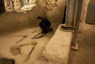 In this photo taken on Dec. 1, 2011, Israel's Antiquities Authority archeologist Eli Shukron sweeps marks carved in the bedrock in an archeological excavation in the city of David near Jerusalem's Old City. The mysterious stone carvings made thousands of years ago and recently uncovered in an excavation underneath Jerusalem have archaeologists stumped. (AP Photo/Sebastian Scheiner)