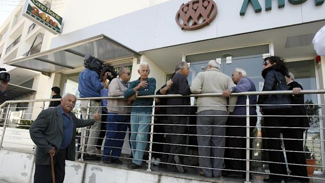 People wait outside a Coop bank branch in Nicosia, Cyprus, Thursday, March 28, 2013. Bank branches across the country were being replenished with cash, and are scheduled to open for six hours at noon (10:00 GMT). Systems were frozen pending the official noon opening. (AP Photo/Philippos Christou)