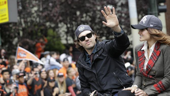 San Francisco Giants pitcher Barry Zito waves while sitting next to his wife, Amber Seyer, during the baseball team's World Series victory parade Wednesday, Oct. 31, 2012, in San Francisco. The team's second championship parade in three years parade ended with a celebration in front of City Hall. (AP Photo/Marcio J. Sanchez)