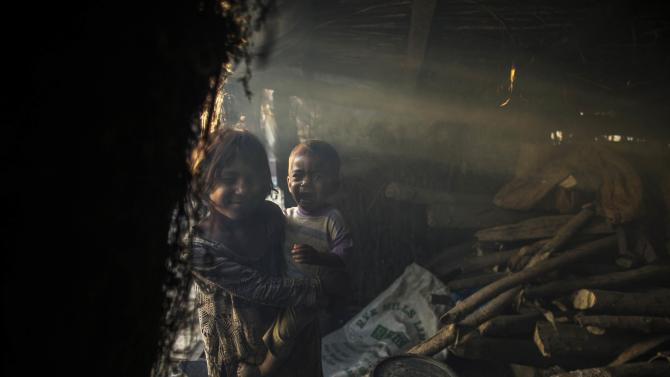 A  girl, whose family moved to Islamabad from Sargodha in Punjab Province to look for work, holds her sibling at her makeshift shelter in Islamabad
